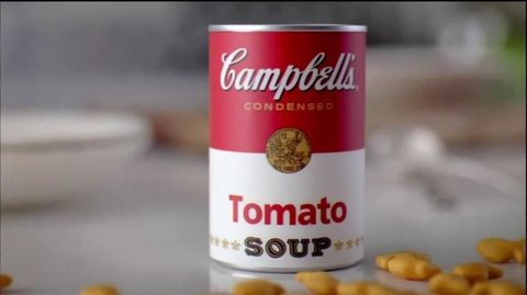 A can of Campbell's Tomato soup surrounding by Goldfish crackers.