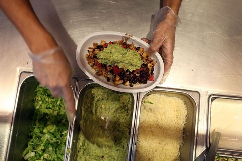 Chipotle worker filling up burrito bowl with guacamole