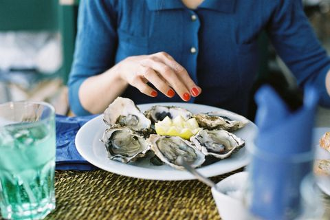Woman eating raw oysters with lemon