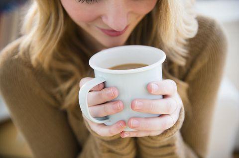 Woman in sweater holding coffee mug