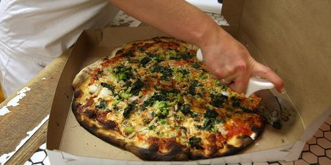 A pizza is prepared for a take out customer at Frank Pepe Pizzeria on Wooster Street in New Haven's Little Italy.