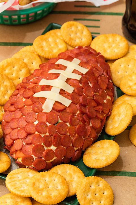 football shaped pepperoni and cheese dip surrounded by crackers