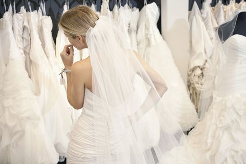 woman trying on wedding dresses in bridal boutique