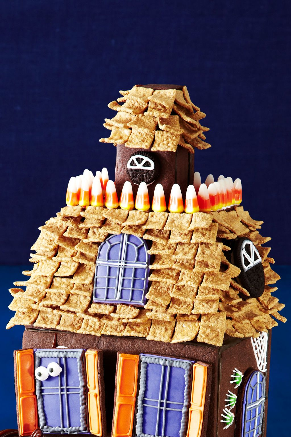 <p><strong>Window and porthole:</strong> Using royal icing, pipe windowpanes on a regular and mini Oreo cookie. Attach to sides of roof and attic with royal icing.</p> <p><strong>Balcony railing:</strong> Use royal icing to stick candy corn around the roof as shown.</p>