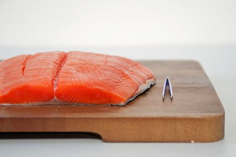 <p>Inspect the salmon both visually and with your fingertips to find any pin bones — small, flexible bones that are sometimes overlooked by the fishmonger — and remove them with a pair of (clean) tweezers.</p>