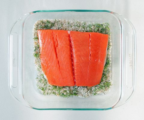 <p>Spread about half of the curing mixture on the bottom of the dish that will house the salmon while it cures. Nestle the salmon on top, skin-side down.</p>