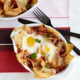 "<p>Traditional huevos rancheros are fried eggs served over tortillas and smothered in sauce and cheese. Here, Grace Parisi bakes eggs, tortilla chips, and cheese in a seasoned tomato sauce in individual gratin dishes. For more sophisticated eaters, swap pepper Jack for the Monterey Jack to get a spicy kick.</p><p><b>Recipe: </b><a href=""/recipefinder/baked-huevos-rancheros-recipe-fw0212"" target=""_blank""><b>Baked Huevos Rancheros</b></a></p>"