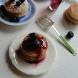 "<b>The Artist:</b> Kim Saulter, <a href=""http://kimsminiatures.blogspot.com/"" target=""_blank"">It's a miniature life</a><br /><br />  Can you believe those fluffy, lightly-browned pancakes and plump, sweet blueberries are actually made out of clay? Kim Saulter started making dollhouse miniatures more than 20 years ago after her first daughter was born. Three years ago she jumped into the world of food miniatures, and she hasn't looked back since. On her blog you'll find recreations of cakes, cookies, pies, muffins, doughnuts, and other treats."