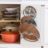 There's nothing more annoying than searching for gone-missing pot toppers in cabinet recesses. The fix: a door-mounted lid rack, such as this one from Organize It, $8. Sauté pans also become simple to slide out thanks to a tiered holder (Miles Kimball, $8). Meanwhile, arrange heftier cookers (cast iron, glass) on bottom shelves to prevent pull-down accidents. <i>Frying pan rack, $8, Miles Kimball; 800-546-2255. Cabinet door lid rack, $8, Organize It; 800-210-7712. Flame Round French oven, $220, Dune stockpot, $70, and stainless steel fry pan, $85, Le Creuset of America; Sur la Table, 800-243-0852.</i>