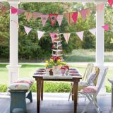 "Place a table on the porch or lawn and brighten the seating with cushions in vibrant prints. Capture spring breezes with <a href=""http://www.countryliving.com/crafts/projects/spring-banner-0407"">banners cut from coordinating fabrics</a> and embellished with aviary motifs. The feather tree centerpiece is adorned with cookies that guests will be given to take home. Tree: <a href=""http://www.seasonsofcannonfalls.com""target=""_new"">Seasons of Cannon Falls</a>. Banner fabric: <a href=""http://www.shopdigs.com""target=""_new"">Digs</a>. Pillows: <a href=""http://www.elizabethallen.com/retail/index.htm""target=""_new"">Elizabeth Allen Atelier</a>."