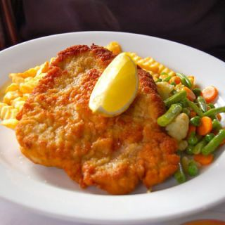 <p>Wiener schnitzel is a very popular dish in Austria that features a boneless piece of meat (usually veal or pork) that has been pounded, breaded, and fried. It's served with a lemon wedge and a potato side.</p>