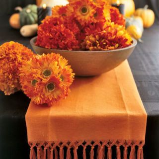 Use silk flowers to create an unexpected (and long-lasting) centerpiece. Choose daisies and marigolds or other flowers in shades evocative of fall foliage, and, using wire cutters, trim the stems to an inch and a half long. Then insert the flower heads into a Styrofoam ball to make a densely packed sphere.