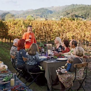 """At Thanksgiving, I always express gratitude for the hard hours the farmers put into this meal."" In late-autumn sun Michael Chiarello toasts guests with his organic Zinfandel. He hosts this ""day-after"" Thanksgiving so that he can see family on the actual day and invite friends when everyone is relaxed. His wife, Eileen, and their son, Aidan, sit at the end of the table."