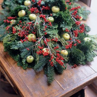 Boughs and berries announce the season. When creating a swag, the trick lies in layering. Starting with a carpet of dense evergreen, such as white fir, lay on something lighter, such as arborvitae or cedar, then contrast with swirling Chamaecyparis branches. Top with winterberry and lady's apples for a glorious statement.