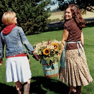 On the way to the party they are hosting on Peone Prairie, not far from Spokane, Wash., Teri Edwards (left) and Serena Thompson carry freshly picked flowers that they have arranged in an old ice-cream-making bucket.