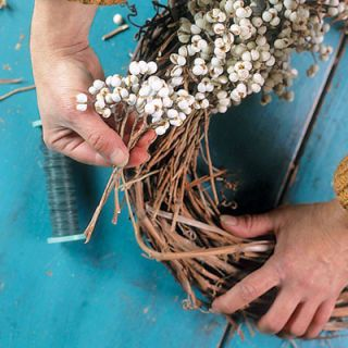 <p>Fasten wire onto wreath. Lay first bunch of berries on wreath form, and bind in with a loose loop of wire wound around. Repeat with another bunch placed directly below, going around and around.</p>