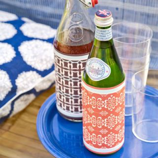 "Sparkling water and lemonade, jars of pickles, even soda bottles become part of the decor when wrapped in patterned paper secured with double-sided tape. Use scraps of gift wrap or wallpaper that match your color scheme, or buy these ready-made sleeves. <br /><br /> <i>(The Gift of Wine kit, $14.95; <a href=""http://search.barnesandnoble.com/booksearch/isbnInquiry.asp?EAN=9780811863469&lkid=J25249592&pubid=K125307&byo=1""target=""_new"">barnesandnoble.com</a>)</i>"