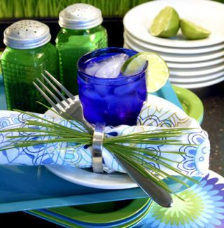 """Glass in the grass"" is a phrase you want to avoid hearing during summer picnic fun. For a much better guest, invite plastic trays to your next outdoor meal. Durable and easy to clean, they're also inexpensive. Lipped trays help contain silverware and condiments as well as provide a clean, flat surface to rest forks in between bites. Bright colors and festive patterns create a retro-chic feel; find melamine if you want a real blast from the past. Once you have a color scheme, flowers and even grass can be handy setting decorations."