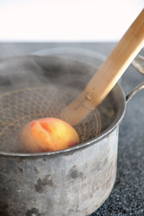 <p>Dunk the peaches into a bath of simmering water that is deep enough to submerge them completely. If the peaches do not stay submerged, turn them occasionally, so that they are heated evenly. After about 40 seconds (a minute if they're slightly underripe), or when the skin begins to slightly pull away on the scored ends, remove the peaches with a slotted spoon or skimmer.</p>