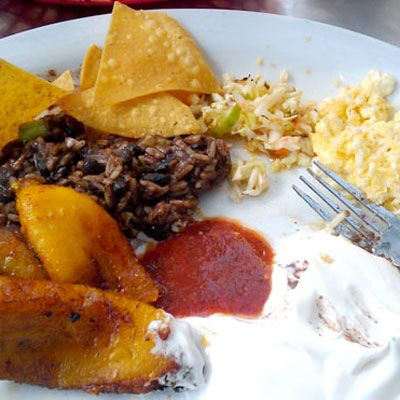 This typical El Salvadorian breakfast made of standard national foods includes fried sweet plantains, casamiento (black beans and rice in an onion sauce) and salsa.