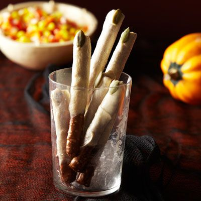 Delicious chocolate dipped pretzels are Halloween ready with the simple addition of pumpkin seeds.