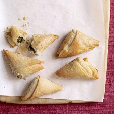 <p>Spinach pies, also called <i>spanakopita</i>, are a Greek classic. They're also easy to find in almost any grocer's freezer section. Simply heating in the oven will take up far less time than wrapping and rolling up all those delicate layers of phyllo dough, and your guests will (no doubt) be impressed.</p>