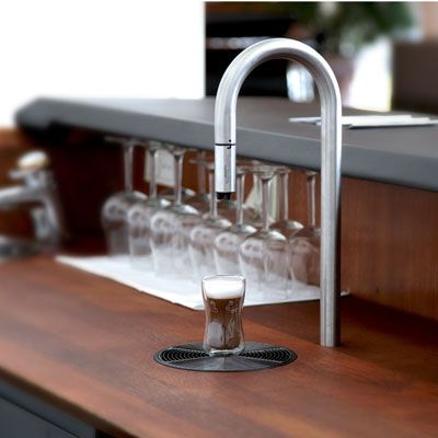 "<p>Incredibly elegant, the Top Brewer is designed to look like a simple faucet, but dispenses much more than water. The stainless steel appliance can be built into any tabletop or countertop, and the end of the tap even contains a small milk frother, so a gourmet cup of coffee or shot of espresso can easily be made all at once, using no other bulky gadgets. This distinctively designed brewer is also tablet and smartphone compatible, meaning you can program your perfect brew directly from your favorite device.</p> <p><a href=""http://www.scanomat.com/coffee-brewers/topbrewer"" target=""_blank"">scanomat.com</a></p>"