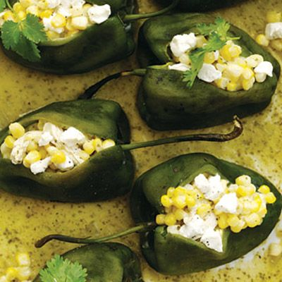 <p>First cultivated south of the border, corn more or less grew up with poblano chiles and tomatillos, two components of this Mexican-influenced dish. The filling in each mellow pepper is a mix of tang and sweetness-poached chicken, nips of goat cheese, sauteed corn, and a green salsa spiked with lime.</p>