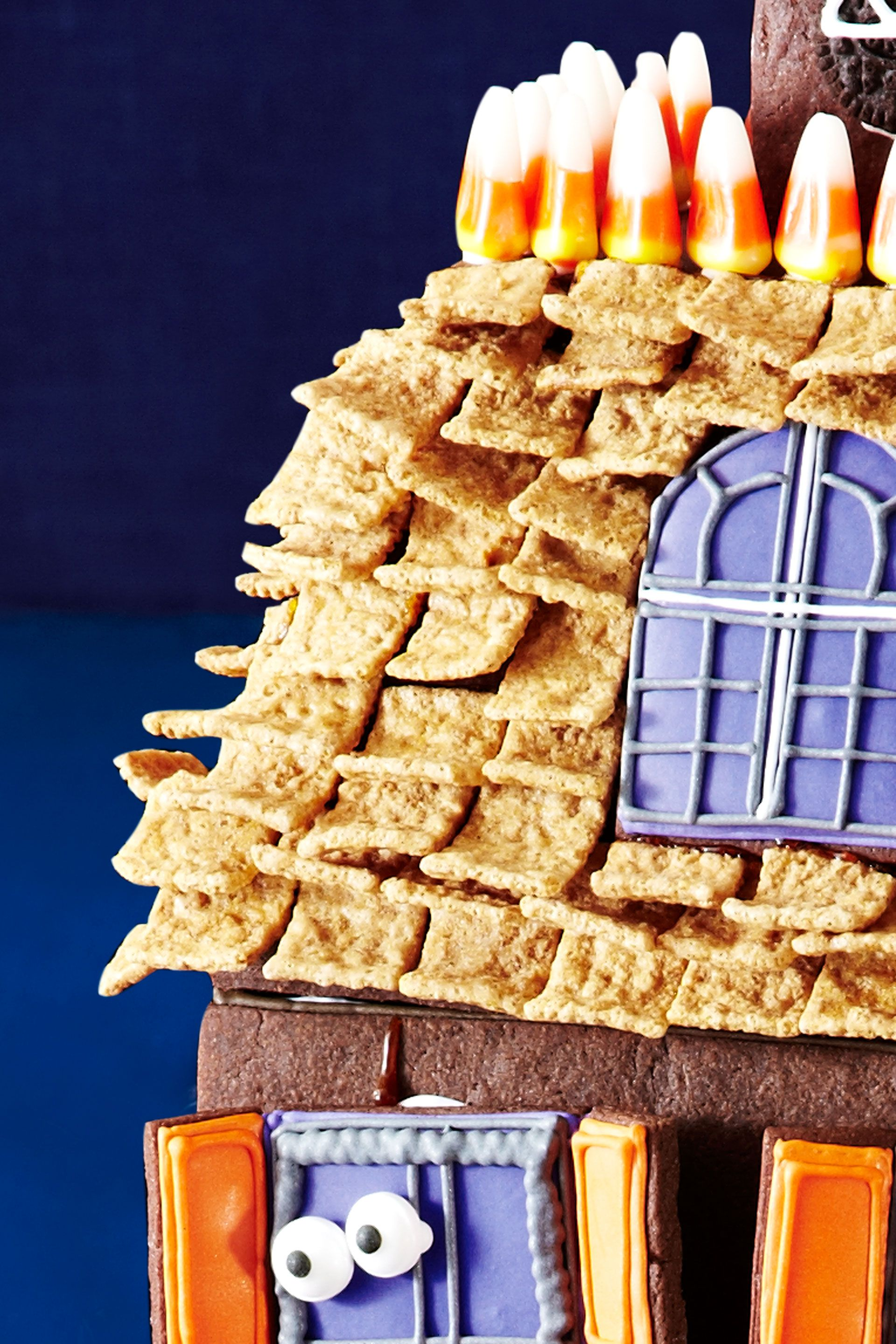 """<p>Starting with the top row, stick Golden Graham Cereal shingles on the roof using melted hard caramel.</p> <p><a href=""""http://www.womansday.com/food-recipes/holiday-recipes/halloween-haunted-house"""" target=""""_self"""">Watch this video to see how to attach the shingles.</a></p>"""