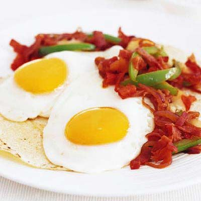 "<p>Sunny side up eggs welcome a warm, peppery tomato salsa in this version of a Mexican favorite.</p><br /><p><b>Recipe: </b><a href=""/recipefinder/huevos-rancheros-spicy-ham-sofrito-recipe-7934"" target=""_blank""><b>Huevos Rancheros with Spicy Ham Sofrito</b></a></p>"