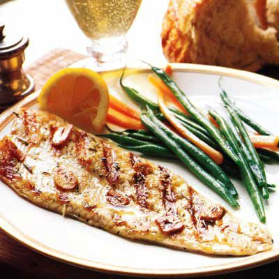"""A simple garlic-and-herb-infused oil combined with wine vinegar acts as both a basting liquid and a sauce for the fish. The trout skin protects the flesh and turns an appealing golden brown during grilling.<br /><br /> <b>Recipe: <a href=""""/recipefinder/tuscan-grilled-trout-recipe-8032""""target=""""_new"""">Tuscan Grilled Trout</a></b>"""