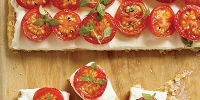 """<p><i>Food & Wine</i>'s Grace Parisi deconstructed the traditional French tomato tart and came up with this amazingly fast and easy hors d'oeuvre. Her stroke of genius: Instead of making individual tarts, she prebakes a large rectangle of puff pastry, spreads on silky pureed ricotta cheese, tops it with oven-roasted cherry tomatoes, cuts, and serves.</p><br /> <p><b>Recipe: </b><a href=""""/recipefinder/tomato-tartlets-recipe"""" target=""""_blank""""><b>Tomato Tartlets</b></a></p>"""