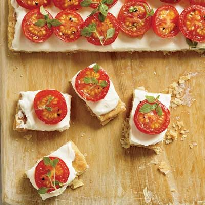 <p><i>Food & Wine</i>'s Grace Parisi deconstructed the traditional French tomato tart and came up with this amazingly fast and easy hors d'oeuvre. Her stroke of genius: Instead of making individual tarts, she prebakes a large rectangle of puff pastry, spreads on silky pureed ricotta cheese, tops it with oven-roasted cherry tomatoes, cuts, and serves.</p><br />