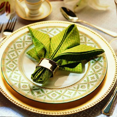 <p>Slip a beautiful napkin ring or tassel around the base of the napkin to hold the fold together.</p><br />