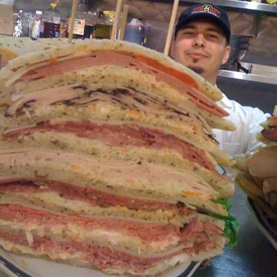 """<p><b>Challenge:</b> Finish the 3 1/2- to 4-pound sandwich layered with six deli meats (no time limit)</p><p><b>Prize:</b> Price of the sandwich plus a free piece of cheesecake</p><p><b>Location:</b> <a href=""""http://www.kennyandziggys.com/"""" target=""""_blank"""">Kenny and Ziggy's Delicatessen</a>, Houston, TX</p><br /><p>The Zellagabetsky, featuring housemade <a href=""""/recipefinder/homemade-corned-beef-vegetables-recipe"""" target=""""_blank"""">corned beef</a>, pastrami, <a href=""""/entertaining-ideas/holidays/thanksgiving/thanksgiving-turkey-recipes"""" target=""""_blank"""">roast turkey</a>, <a href=""""/recipefinder/coriander-dusted-roast-beef-recipe-cd9678f8-0b31-43f9-a3c400efe76110da"""" target=""""_blank"""">roast beef</a>, salami, and tongue layered with <a href=""""/entertaining-ideas/parties/picnics/coleslaw-recipes"""" target=""""_blank"""">coleslaw</a>, Russian dressing, and sweet red pepper on special-cut rye, has been vexing hungry challengers for the past 15 years. One of only three winners, Shaquille O'Neal, a then rising star of the Orlando Magic, ate the sandwich so fast, he was awarded with not just a slice, but the whole <a href=""""/recipes/cooking-recipes/ultimate-cheesecake-recipes"""" target=""""_blank"""">cheesecake</a>.</p>"""