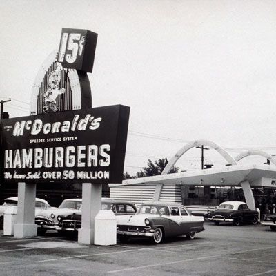 "<p><b>Year Opened:</b>1940 </p> <p><b>First Location:</b> San Bernadino,  CA</p> <p><b>Bite of History:</b>  Dick and Mac McDonald started McDonald's as a very different concept. Instead of hamburgers, the brothers created a drive-in restaurant with a comprehensive barbecue menu. They soon scrapped that idea in favor of a 9-item menu: hamburger, cheeseburger, three soft drinks, milk, coffee, potato chips, pie, French fries, and milkshakes. By 1952, word of their success (and a cover story in <i>Restaurant Magazine</i>) traveled as far as Arizona, where they allowed Neil Fox to launch a carbon copy restaurant with the signature golden arches. Three years later, Ray Kroc, a ""Multimixers"" milkshake machine salesman, took the reigns as official franchising agent. On April 15, 1955, the first franchise opened in Des Plaines, IL, selling fries for 10 cents and burgers for 15 cents. </p>"