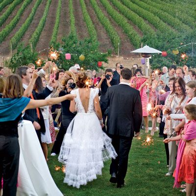 A passion for Latin foods and music combined with a love of the Pacific Northwest inspired Andrea Rutledge and Dennis Haupt to wed outdoors in a flurry of vibrant color. Last September, at an Oregon vineyard ripe with fruit and tradition, bridesmaids dressed in fuchsia, purple, and red surrounded the bride. A band playing Cuban melodies filled the early evening air with music. And long tables, thoughtfully placed east to west, ensured that no guest was denied views of the spectacular pink and orange sunset.