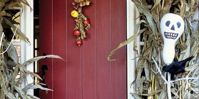 """Make your front door season-appropriate, framing it with dried corn husks and a garland of oak leaves. Ghostly bottle-gourd scarecrows were painted white, with features added in black felt tip, and then speared on sticks and """"planted"""" in Styrofoam blocks inside urns."""