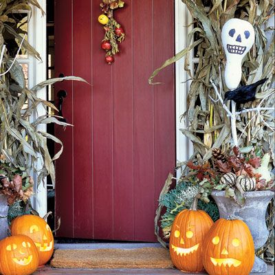 "Make your front door season-appropriate, framing it with dried corn husks and a garland of oak leaves. Ghostly bottle-gourd scarecrows were painted white, with features added in black felt tip, and then speared on sticks and ""planted"" in Styrofoam blocks inside urns."