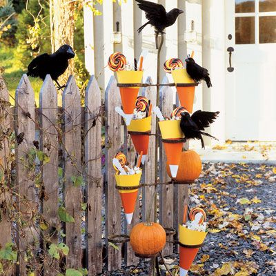 "Halloween entertaining is all about scaring up creative ways to celebrate the holiday. Neither children nor grown-ups want to miss out on trick-or-treating. Treat every guest to a surprise right at the door — perhaps with candy-filled cones nestled in a vintage plant stand aflutter with feathered crows.<br /><br /><b>Candy Cone How-to's</b><br /><br /><b>1.</b> To create a cone about 10 inches long, first wrap an 8 1/2"" by 11"" sheet of heavyweight white paper on the diagonal. Trim excess paper. Use this as a template to cut as many cones as desired.<br /><br /><b>2.</b> Shaping each cone according to the template, use pinking shears to cut a band of glossy orange paper about 4 inches wide for the middle of the cone, and a band of yellow paper about 3 inches wide for the top. Affix the orange and yellow bands to the white base, then join the ends of the cone together, using double-sided tape."
