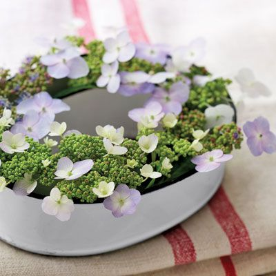 "Ring around the posy: An oval enamelware mold provides the perfect ""nest"" for small flowers. Anchor stems in florist's foam or nestle inside glass baby-food jars."