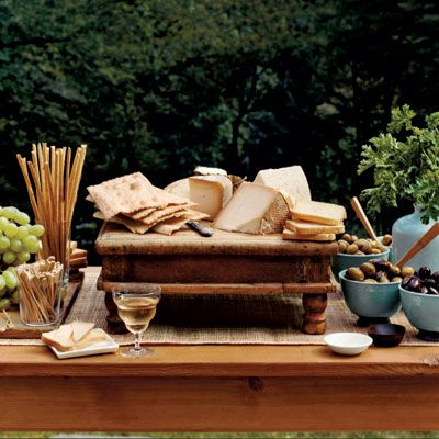 "Lynn Butler Beling set up the buffet outdoors. ""I wanted it to be visually interesting,"" she says, ""so I varied the heights of things, putting tall breadsticks on one side and foliage in a vase on the other. In between, I placed low bowls and a medium-high cheese board."" <br>TABLE: <a href=""http://www.curranantiques.com/""target=""_blank"">JAMES CURRAN ANTIQUES</a>. ALL TABLEWARE: <a href=""http://theproductgallery.com/"">THE PRODUCT GALLERY</a>."