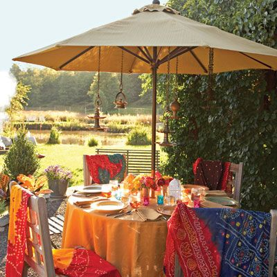 To set the mood for her cookout, cookbook author and Indian cooking authority Maya Kaimal keeps the table colorful and slightly exotic, much like the spices used to prepare the meal. A saffron tablecloth anchors a table set with jewel-toned votives, cutwork lanterns, and compact bouquets picked from the garden. When dining alfresco, Maya keeps cushions on hand to soften the seats of outdoor furniture and incorporates multiple light sources, such as paper lanterns, votives, and oil lamps. She also drapes vintage cotton shawls over each chair in case the night air gets chilly.