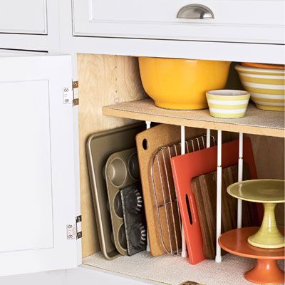 <p>The first step to ending kitchen chaos: Store pots and pans near the stove and oven for easy access. Then, stow cookware according to function (colanders with pasta pots, mixing bowls with bakeware). Prevent flat items like cookie sheets and cutting boards from piling up, too, with tension curtain rods spaced between firmly installed shelves. <i>Goldtouch jelly-roll pan, $25, and muffin pan, $29; Williams-Sonoma, 800-541-2233</i></p>