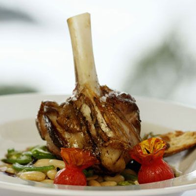 <p><strong>SERVINGS</strong></p><p>4</p><br /><p><strong>INGREDIENTS</strong></p><p>4 lamb shanks, about 1 pound each</p><p>1 cup unbleached all purpose flour, for dredging</p><p>1 tablespoon olive oil</p><p>4 garlic cloves, peeled and chopped</p><p>1 pound wild mushrooms, chopped (shiitakes)</p><p>1/2 cup red wine</p><p>2 cups vegetable broth</p><p>1 teaspoon chopped fresh rosemary</p><p>Salt and pepper to taste</p><br /><p><strong>PREPARATION</strong></p><p>1. Preheat the oven to 350 degrees F.</p><br /><p>2. Dredge the lamb shanks in flour and set aside.</p><br /><p>3. In a roasting pan over high heat, heat the olive oil until smoking hot.</p><br /><p>4. Brown the lamb shanks for about 4 or 5 minute per side or until well caramelized.</p><br /><p>5. Add the garlic and mushrooms and cook until tender, about 4 minutes.</p><br /><p>6. Add the red wine and cook until the wine has evaporated, about 4 minutes. Add the vegetable broth and bring the mixture to a boil.</p><br /><p>7. Add the rosemary and salt and pepper. Cover the pan with a lid or aluminum foil and place in the preheated oven. Roast until the lamb is tender, about 1 to 1 1/2 hours. Serve with the pan sauce.</p>