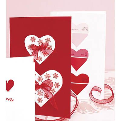 """<p>Left: Start with a blank red card. Cut out two white paper hearts, then stamp them with a small rubber stamp (we used a snowflake design). Paste the hearts to the card. Finally, affix a small bow to the center of each heart with craft glue.</p><br /><p>Right: This graphic love note is a white card decorated with three hearts cut out of a red-toned paint strip. For an extra-cute touch, look for chips with names like """"blush"""" or """"coral kiss.""""</p>"""