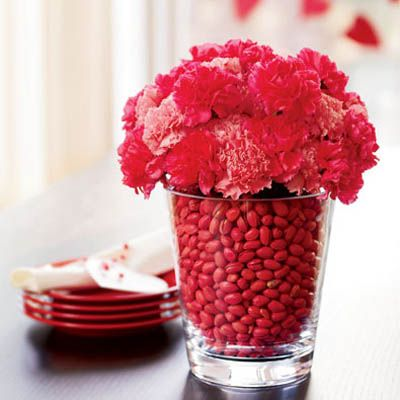 <p>Hit the grocery aisles for a festive, budget-friendly centerpiece! You'll need two vases, one that's clear and big enough to hold the smaller vase.</p>  <br /><p>Fill the smaller one with water and a bunch of light and dark pink carnations, and place inside the larger vase. Fill up the space between the vases with red pistachios!  </p>