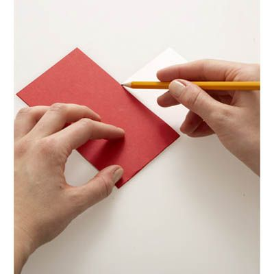 "<p>Cut a 3"" by 11"" strip of paper from a piece of colored card stock. Fold the strip in half, so that it measures 3"" by 5 1/2"". Repeat this step with a second color of card stock.</p>  <br /><p>Lay one piece of folded card stock on the table in front of you so the fold is to your left. Lay the other folded piece of card stock on top of it at right angles, so the second card's fold is facing you. Mark a light pencil line on the bottom card along the right-hand edge of the top card (see photo).</p> <br /><p>Flip the whole thing over and mark the new bottom card along the new top card's right-hand edge in the same way. </p>"