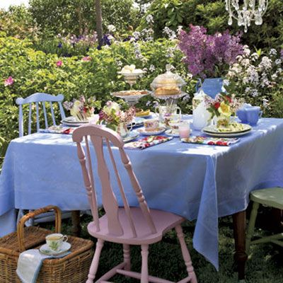 Shades of pastel and an abundance of flowers are the foundation of a fanciful backyard tea party. A jug of fragrant lilac branches, floral-print napkins, silver teaspoons, and tiered serving pieces all add a touch of romantic grandeur to an easy afternoon.