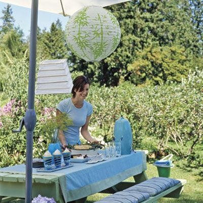 A picnic table set with blues and greens under a canopy is a welcoming retreat from & Summertime Table Settings - How to Set a Summertime Table